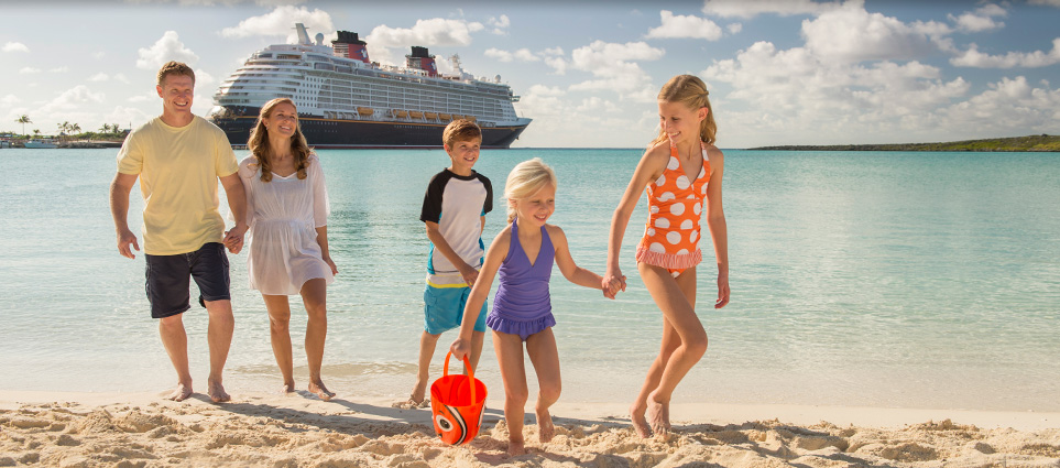 Family walking on beach with Disney Cruise Ship in background
